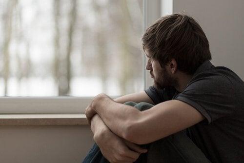 Smutny mężczyzna siedzi przy oknie