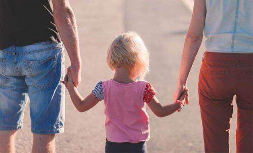 Rodzice trzymają dziecko za ręce