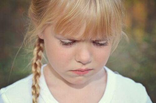 Smutna dziewczynka patrzy w dół