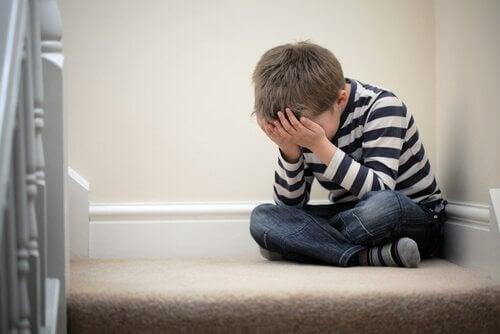 Smutne dziecko z rękami na twarzy