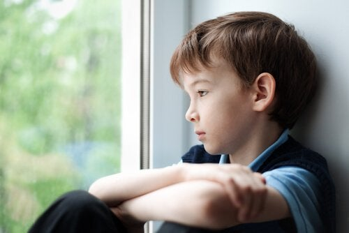 Smutny chłopiec patrzący przez okno