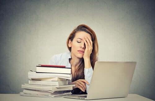 Przemęczona kobieta przy biurku - syndrom Kasandry