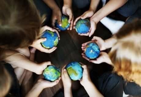 Grupa ludzi trzyma globusy w dłoniach