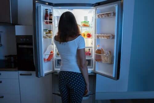 Kobieta jedząca z lodówki w środku nocy