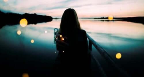 Egzystencjalna pustka - kobieta nad rzeką przy zachodzie słońca