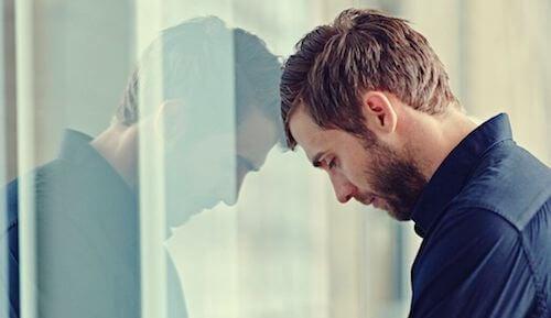 Mężczyzna z głową opartą o ścianę - musi z kimś rozmawiać