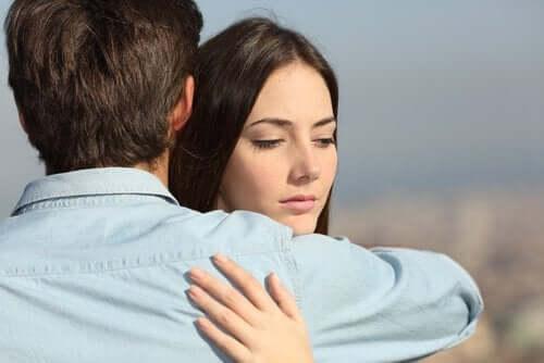 Zamyślona kobieta przytulająca mężczyznę