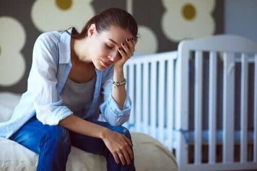 Zmęczona matka przy łóżeczku dziecka