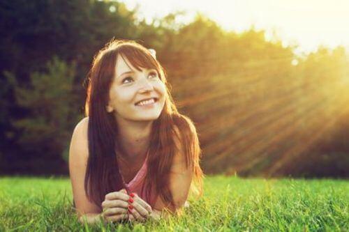 Kobieta na trawie wie, że słońce to lekarstwo na depresję i niepokój