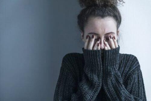 Kobieta zakrywa twarz dłońmi