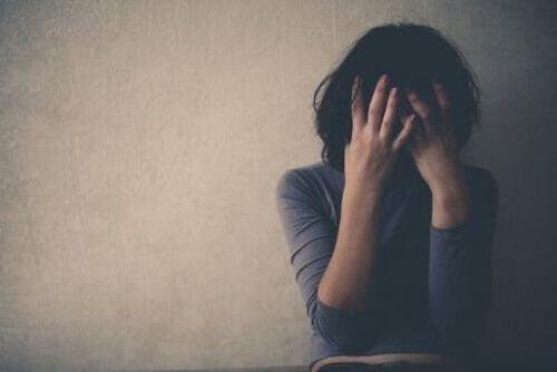Załamana kobieta ukrywa twarz w dłoniach