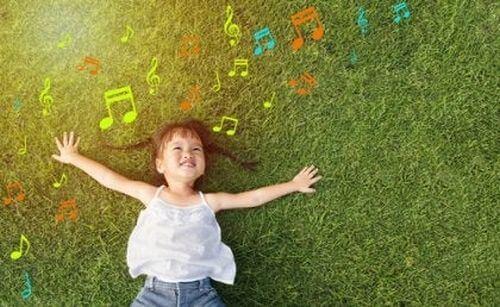 Dziecko leży na trawie i ogląda kolorowe nuty - wpływ muzykoterapii
