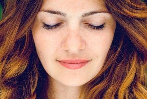 Kobieta uśmiecha się z zamkniętymi oczami