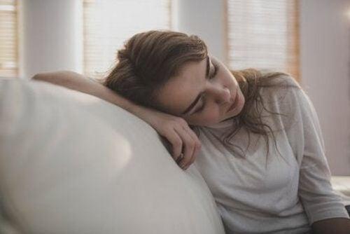 Zmęczona kobieta opiera głowę o oparcie sofy