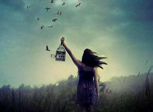 Kobieta wypuszcza ptaszka z klatki