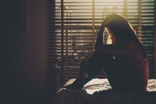 Smutna dziewczyna siedzi na łóżku