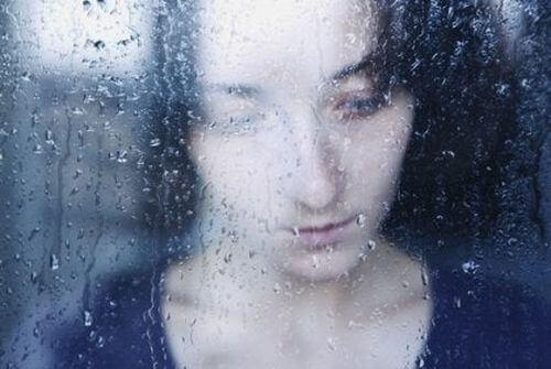 Smutna kobieta za mokrą szybą