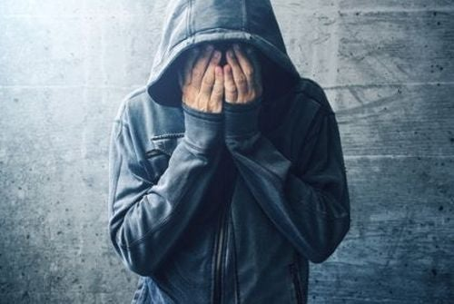 Uzależnienie - mężczyzna w kapturze zakrywa twarz