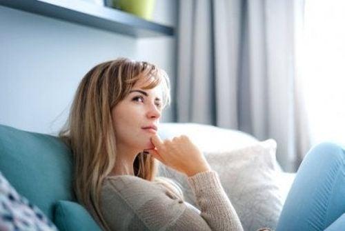 Zamyślona kobieta na kanapie