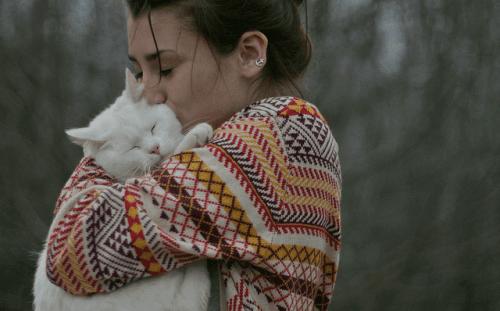 Kobieta trzyma kota w objęciach