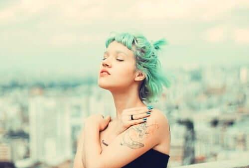 Kobieta o zielonych włosach obejmuje się rękami