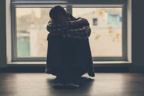 Załamany mężczyzna siedzi skulony