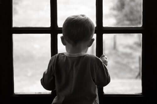 Małe dziecko patrzące przez drzwi