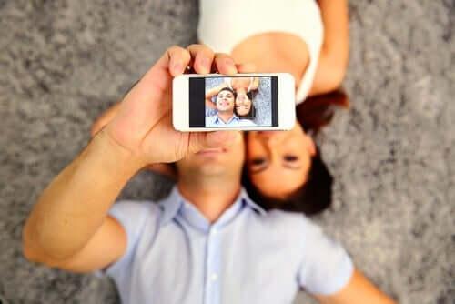 Mężczyzna robiący selfie z kobietą - pragnienie udawania w mediach społecznościowych