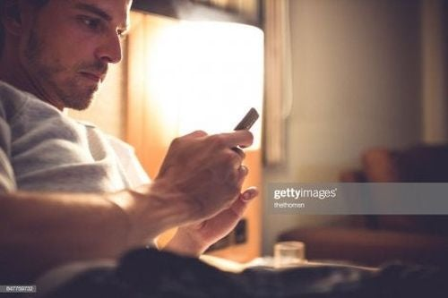 Mężczyzna patrzy w telefon - uzależnienia behawioralne