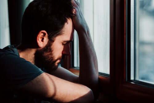 Smutny mężczyzna wyglądający przez okno