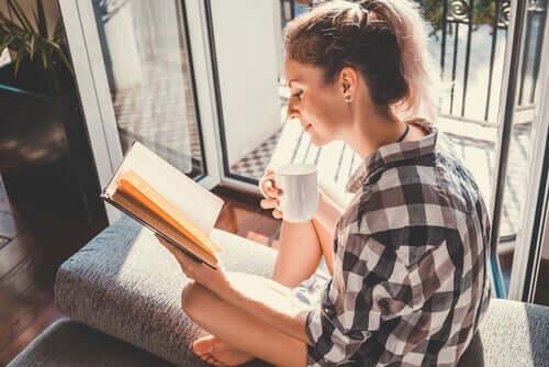 Kobieta czytająca przy balkonie - czytanie poprawia inteligencję emocjonalną