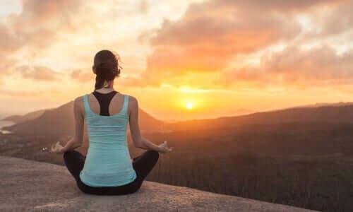 Kobieta relaksuje się na tle zachodzącego słońca