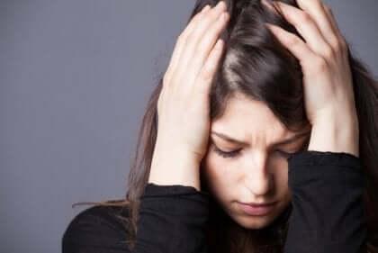 Kobieta trzymająca się za głowę - procesy chemiczne związane z lękiem