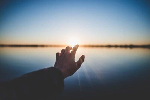 Dłoń na tle zachodzącego słońca