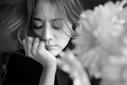 Smutna kobieta z kwiatem