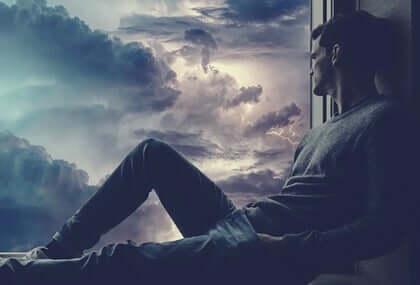 Smutny mężczyzna patrzący przez okno - tęsknota za osobą, której nie ma