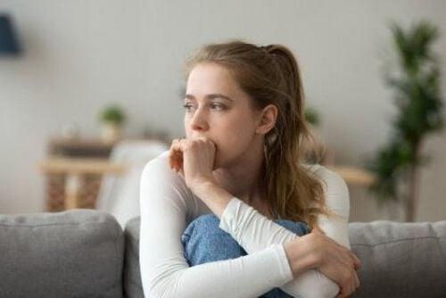Zamyślona kobieta siedzi na sofie
