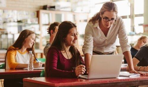Nauczycielka patrząca w komputer uczennicy