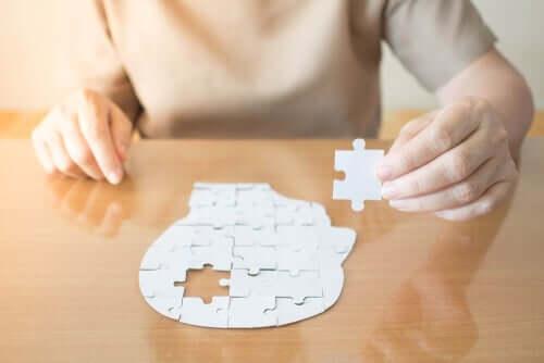 Osoba układająca głowę z puzzli