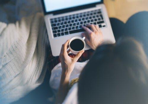 Kobieta z kawą pisząca na komputerze