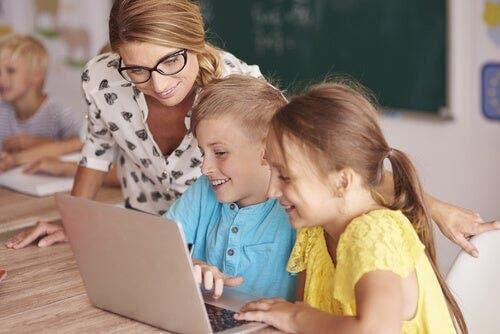 Nauczycielka z uczniami przy komputerze
