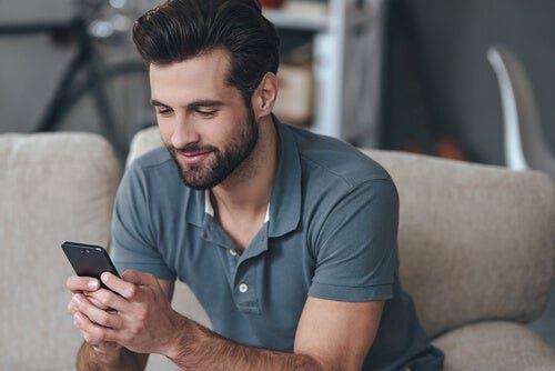 Uśmiechnięty mężczyzna patrzący na komórkę