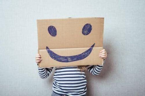Dziecko za kartonem z narysowanym uśmiechem
