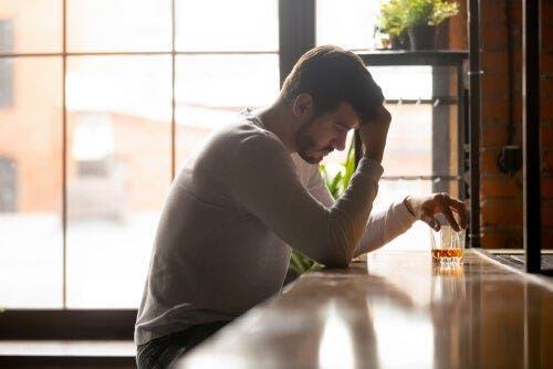 Mężczyzna przy barze ze szklanką alkoholu - oszukiwanie samego siebie i alkoholizm