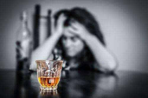 Załamana kobieta patrząca na alkohol