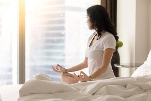 Kobieta medytująca na łóżku - rutyna Miracle Morning
