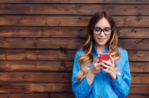 Kobieta pisząca na komórce - serwisy społecznościowe wpływają na poczucie własnej wartości