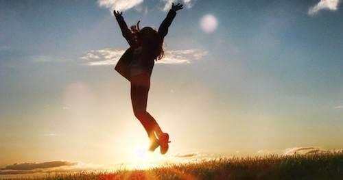 Kobieta skacząca o zachodzie słońca