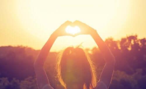 Kobieta układająca serce z dłoni