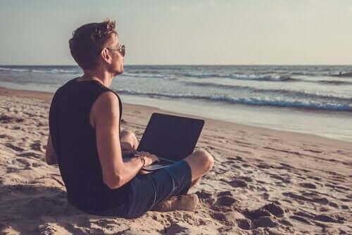 Mężczyzna z laptopem na plaży